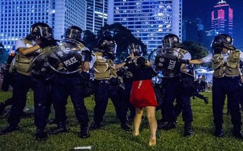 Sáng sớm nay, cảnh sát chống bạo động của Hồng Kông đã xả hơi cay và  dùng dùi cui để trấn áp những người biểu tình đòi bầu cử dân chủ, trong  khi người biểu tình dựng các rào chắn trên các tuyến phố quan trọng - Ảnh: AFP/Getty/CNBC.<br>