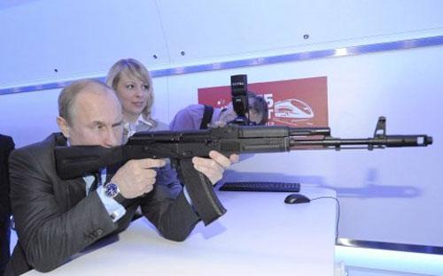 Tổng thống Nga Vladimir Putin ngắm một khẩu súng trường tại một trung tâm nghiên cứu ở Moscow hồi tháng 4/2012 - Ảnh: RIA Novosti/Reuters/BI.<br>