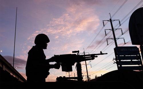 Một binh sỹ Thái Lan đứng gác ở Bangkok sáng sớm ngày 20/5 - Ảnh: AP.<br>
