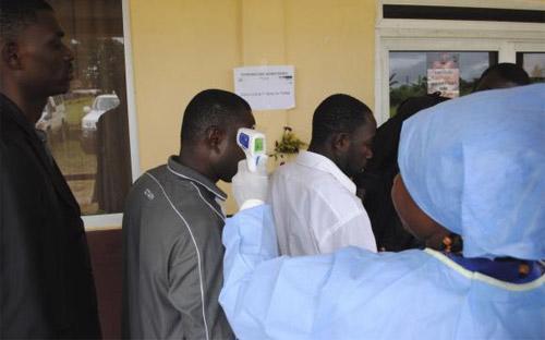 Một nhân viên y tế đang kiểm tra nhiệt độ cơ thể những người tới tham dự một cuộc họp báo về Ebola ở Monrovia, Liberia ngày 3/10 - Ảnh: Reuters.<br>