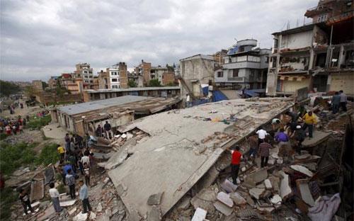 Người dân tập trung gần một tòa nhà bị sập trong trận động đất ở Kathmandu hôm 25/4 - Ảnh: Reuters.