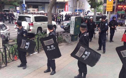 Cảnh sát đứng gác bên ngoài hiện trường vụ tấn công khủng bố ở Urumqi ngày 22/5 - Ảnh: AP.<br>