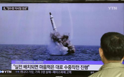 Một người Hàn Quốc xem bản tin truyền hình phát những hình ảnh do Triều Tiên công bố về vụ phóng tên lửa đạn đạo từ tàu ngầm vào cuối tuần vừa rồi - Ảnh: AP/Bloomberg.<br>