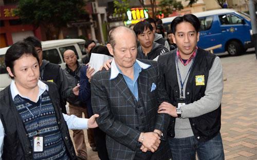 Alan Ho (giữa), người điều hành đường dây mại dâm lớn nhất Macau, bị cảnh sát bắt - Ảnh: AP.<br>