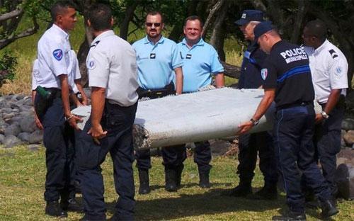 Các nhà chức trách và mảnh vỡ được tìm thấy trên đảo Reunion hồi tháng 7. Mảnh vỡ này đã được Pháp xác nhận là của chuyến bay mất tích MH370 - Ảnh: Reuters.<br>