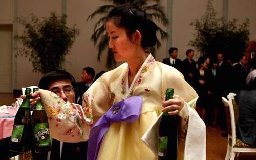 Một nữ nhân viên phục vụ đang tiếp bia tại một bữa tiệc chiêu đãi do Chính phủ Triều Tiên tổ chức ở Bình Nhưỡng - Ảnh: CNBC/Getty.<br>