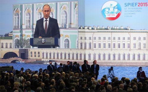 Hình ảnh Tổng thống Nga Vladimir Putin phát biểu phát trên một màn hình lớn tại Diễn đàn Kinh tế Thế giới St. Petersburg, Nga - Ảnh: Bloomberg.<br>
