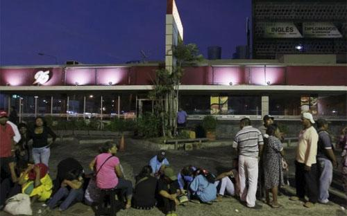 Người dân Venezuela xếp hàng xuyên đêm trước cửa siêu thị để chờ mua thực phẩm - Ảnh: Reuters.<br>