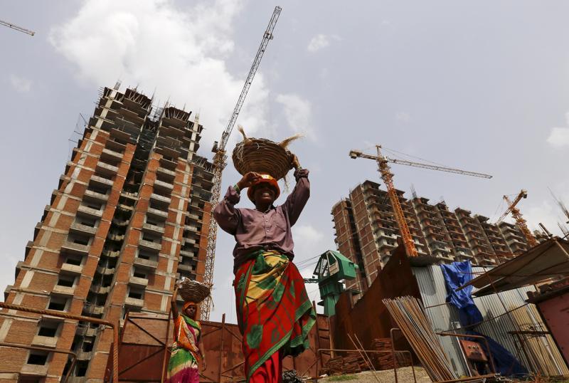 Công nhân làm việc trên một công trường xây dựng ở thủ đô New Delhi, Ấn Độ&nbsp; - Ảnh: Reuters.<br>