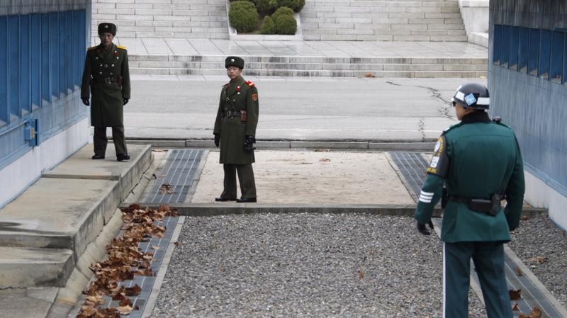 Một binh sỹ Hàn Quốc (trái) đối diện với hai binh sỹ Triều Tiên tại khu phi quân sự giữa hai miền bán đảo Triều Tiên vào tháng 12/2011 - Ảnh: Reuters/NPR.<br>