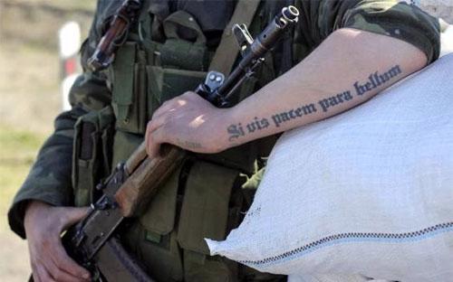"""Một người lính Ukraine tại chốt gác ở Salkovo, gần Crimea, với dòng chữ xăm trên tay có nghĩa: """"Nếu muốn hòa bình, phải chuẩn bị cho chiến tranh"""" - Ảnh: Reuters.<br>"""