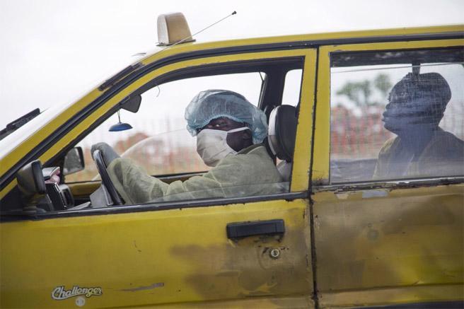 Một người lái xe taxi đang đưa một phụ nữ bị ốm tới khám tại một trung tâm điều trị Ebola ở thủ đô Monrovia của Liberia hôm 4/9. <br>