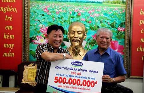 Ông Nguyễn Thanh Tú - Chủ tịch Công đoàn Vinamilk (bên trái) đại diện công ty trao tặng 500 triệu đồng cho ông Trần Thành Long - Chủ tịch Hội Bảo trợ Bệnh nhân nghèo Tp.HCM để giúp trẻ em bị bệnh tim bẩm sinh.