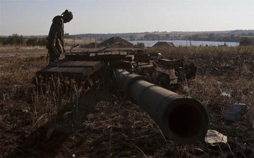 Một tay súng phe ly khai Ukraine đứng cạnh chiếc xe tăng đã bị phá nát - Ảnh: Reuters.<br>