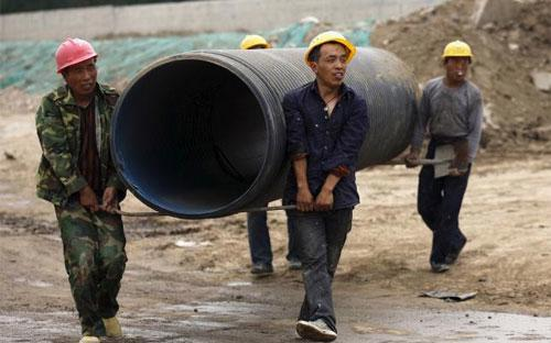 Công nhân làm việc trên một công trường xây dựng ở Trung Quốc tháng 3/2015 - Ảnh: Reuters.<br>