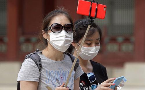 Đến nay, WHO chưa khuyến nghị giảm đi lại tới Hàn Quốc, nhưng hàng nghìn du khách quốc tế đã hủy chuyến đi tới nước này - Ảnh: Getty/Bloomberg.<br>