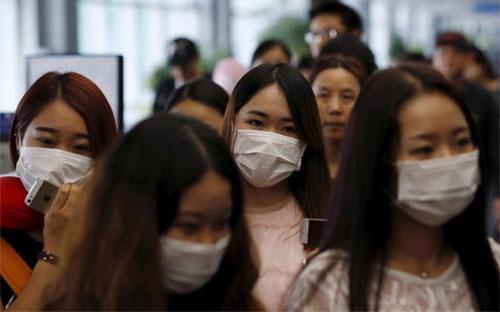Hành khách đeo khẩu trang để tránh lây nhiễm MERS tại Sân bay Quốc tế Incheon, Hàn Quốc - Ảnh: Reuters.<br>