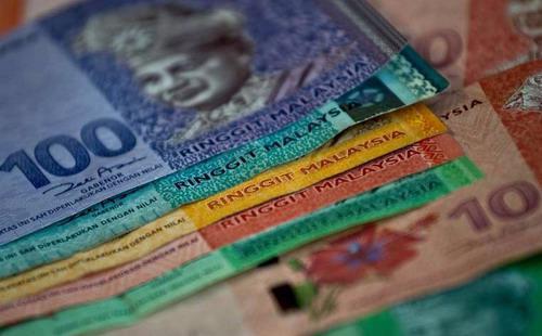 Đồng ringgit chịu tác động mạnh từ việc giá hàng hóa giảm sâu và căng thẳng chính trị liên quan đến Thủ tướng Najib Razak xung quanh những cáo buộc về biển thủ công quỹ - Ảnh: Reuters.