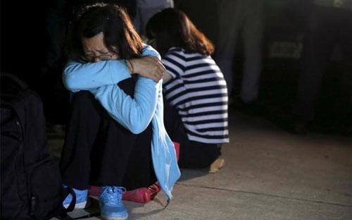 Thân nhân hành khách tàu Ngôi sao phương Đông ngày 4/6 ngồi đợi tin bên bờ sông Dương Tử nơi con tàu bị chìm hôm 1/6 - Ảnh: Reuters.<br>