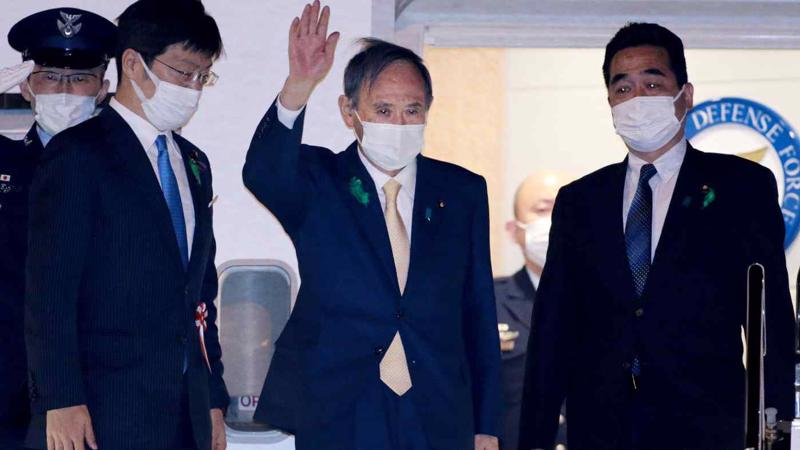 Thủ tướng Nhật Yoshihide Suga vẫy tay chào khi rời sân bay Haneda (Tokyo) bay tới Washington để gặp Tổng thống Mỹ Joe Biden - Ảnh: Nikkei Asia