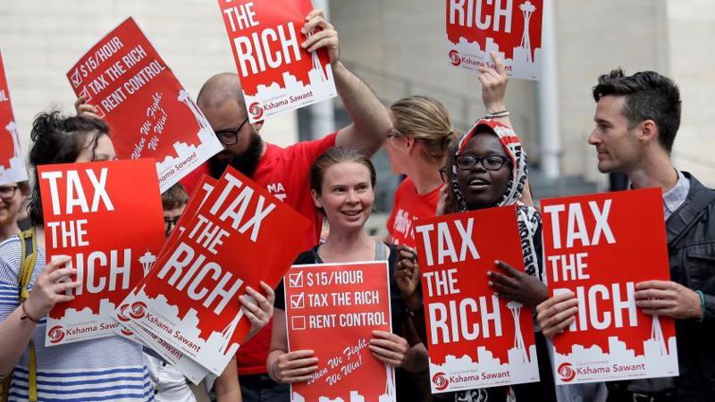 Người biểu tình giơ biểu ngữ kêu gọi đánh thuế người giàu ở Mỹ - Ảnh: LAT.