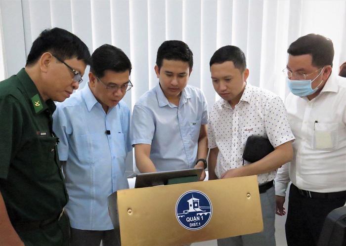 Ông Nguyễn Văn Dũng (thứ hai, từ trái sang) cùng các đại biểu trải nghiệm hệ thống định danh khách hàng điện tử tại UBND Quận 1.