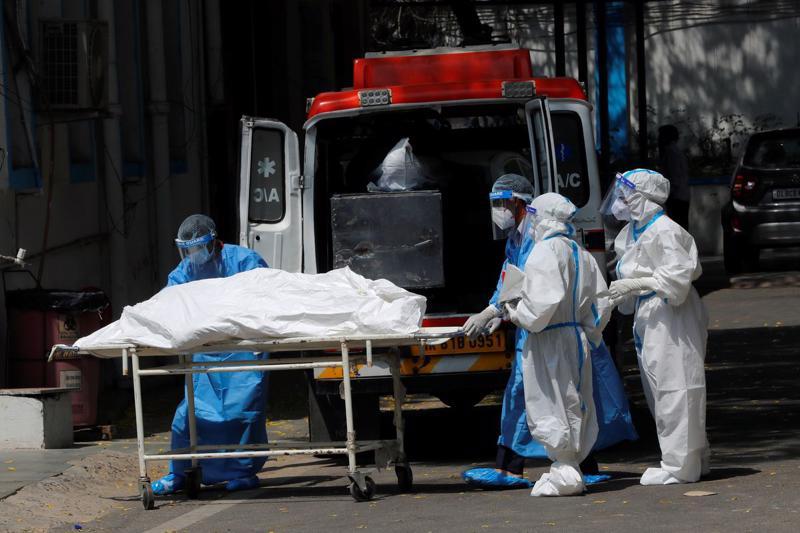 Nhân viên tang lễ di chuyển thi thể một bệnh nhân Covid tử vong ở New Delhi, Ấn Độ, ngày 5/5 - Ảnh: Reuters.