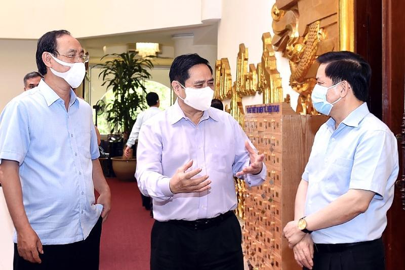 Thủ tướng Phạm Minh Chính trao đổi với lãnh đạo Bộ Giao thông vận tải bên lề cuộc họp - Ảnh: VGP.
