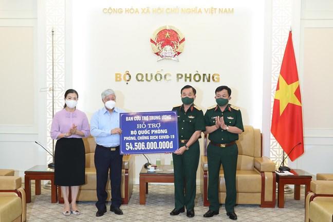 Chủ tịch Ủy ban nhân dân MTTQ Việt Nam Đỗ Văn Chiến trao số tiền hỗ trợ cho Thượng tướng Hoàng Xuân Chiến, Thứ trưởng Bộ Quốc phòng. Ảnh - Quang Vinh.