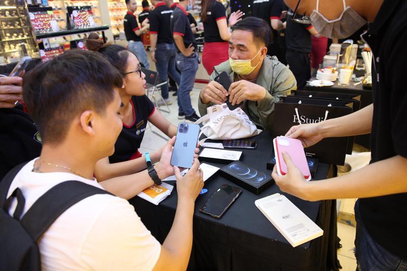 Nhiều khách hàng trẻ thích thú chiếc iPhone 12 pro trên tay tại FPT Shop