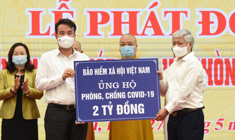 Tổng Giám đốc Bảo hiểm xã hội Việt Nam Nguyễn Thế Mạnh (trái) trao tiền ủng hộ tới Chủ tịch Ủy ban Trung ương Mặt trận Tổ quốc Việt Nam Đỗ Văn Chiến. Ảnh - MTTQ Việt Nam.