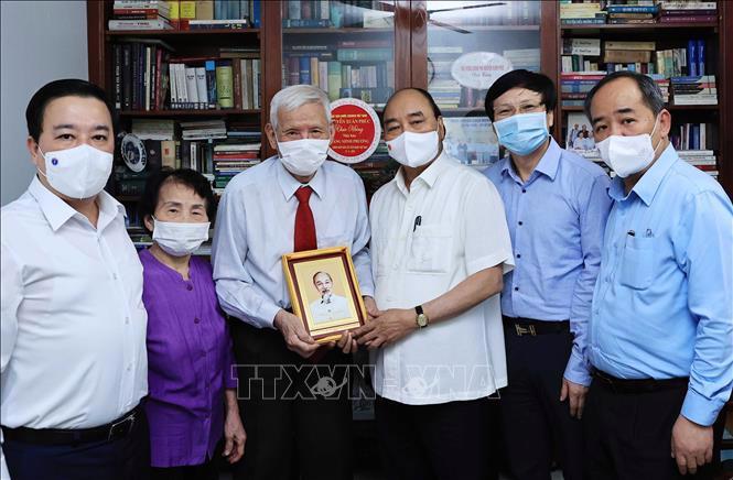 Chủ tịch nước Nguyễn Xuân Phúc đến thăm hỏi và tặng quà cho nhà báo Đặng Minh Phương - Ảnh: TTXVN