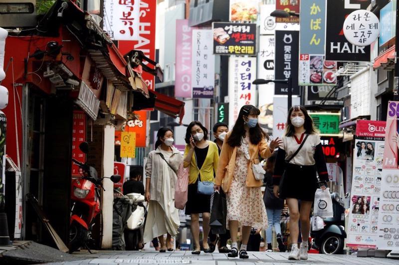 Người đi bộ tại quận mua sắm Myeongdong tại Seoul, Hàn Quốc vào tháng 5 - Ảnh: Reuters