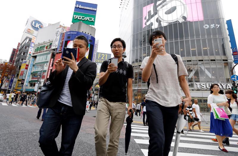 Người dùng smartphone trên đường phố ở Nhật Bản - Ảnh: Kyodo
