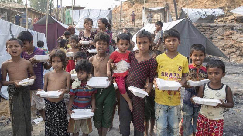 Trẻ em nhận thức ăn từ các tổ chức phi chính phủ và tổ chức xã hội sau vụ hỏa hoạn tại một trại tị nạn ở Ukhia, Cox's Bazar, Bangladesh ngày 24/3/2021 - Ảnh: Getty Images
