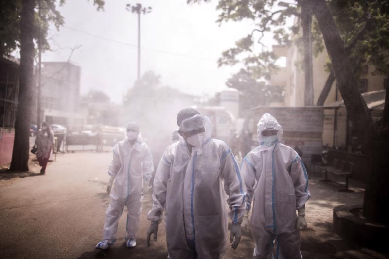 Nhân viên y tế tuyến đầu phun khử khuẩn tại một bệnh viện dã chiến ở bang Uttar Pradesh, Ấn Độ, tháng 5/2021 - Ảnh: Bloomberg.