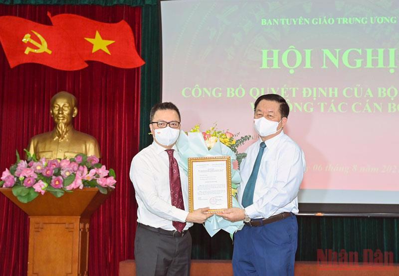 Ông Nguyễn Trọng Nghĩa, Trưởng Ban Tuyên giáo Trung ương trao quyết định và tặng hoa, chúc mừng Phó Trưởng Ban Tuyên giáo Trung ương Lê Quốc Minh. Ảnh - Duy Linh.