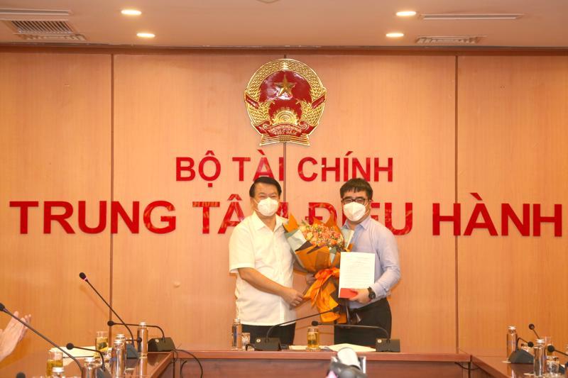 Thứ trưởng Bộ Tài chính Nguyễn Đức Chi (bên trái) trao quyết định và tặng hoa chúc mừng ông Ngô Việt Trung.