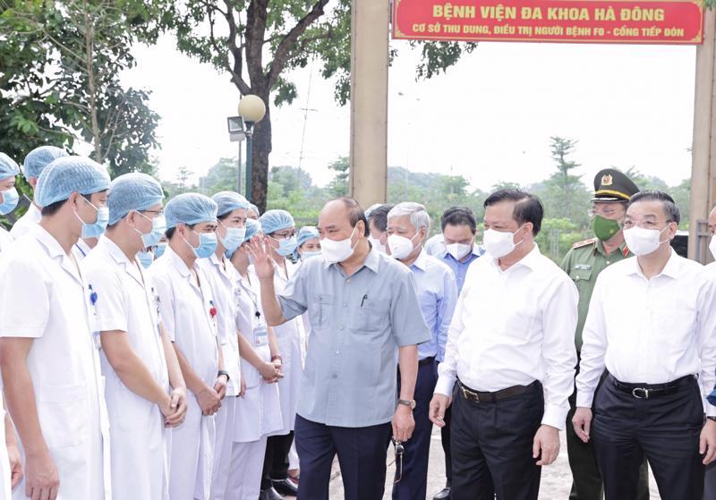 Chủ tịch nước Nguyễn Xuân Phúc tặng quà các nhân viên y tế làm việc tại cơ sở thu dung, điều trị bệnh nhân Covid-19 của Bệnh viện Đa khoa Hà Đông tại phường Hoàng Liệt, quận Hoàng Mai - Ảnh: VGP