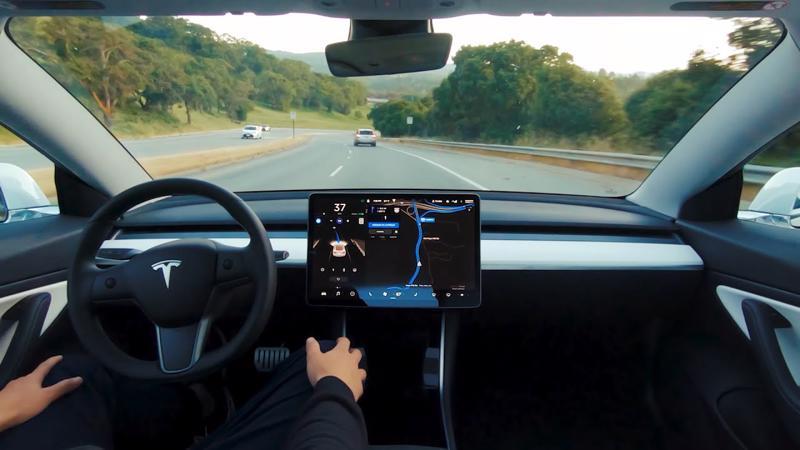 Một tài xế đang thử nghiệm công nghệ tự lái trên xe Tesla - Ảnh: Autoweek.