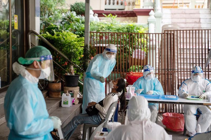 Các nhà sư và tình nguyện viên làm xét nghiệm Covid miễn phí cho người dân tại một ngôi chùa ở Bangkok, Thái Lan - Ảnh: Bloomberg.