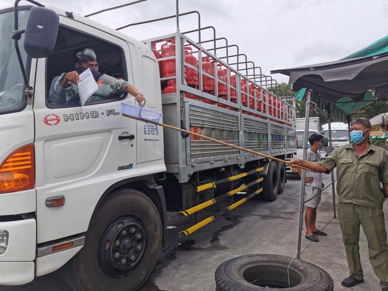 Các phương tiện vận chuyển hàng thiết yếu trình giấy tờ để kiểm soát tại bãi tập kết hàng hóa, trạm thu phí T2, quận Cái Răng. Ảnh: Báo Cần Thơ