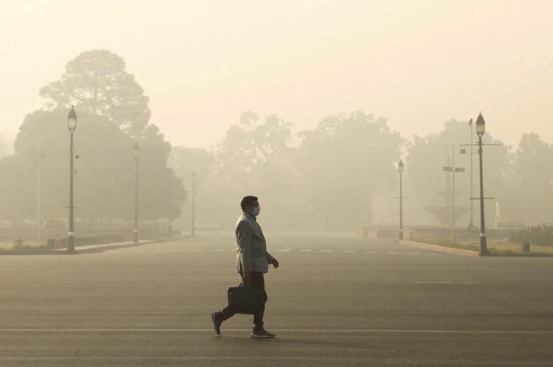 Một người đàn ông bước đi trong bầu không khí đầy khói mù ở New Delhi, Ấn Độ vào buổi sáng ngày 23/12/2020 - Ảnh: Reuters.
