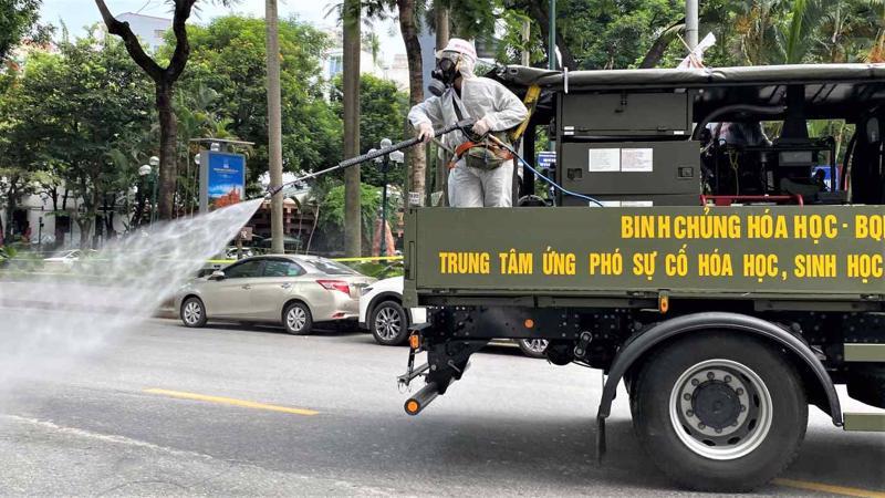 Phun thuốc khử trùng trên đường phố ở Hà Nội - Ảnh: Reuters