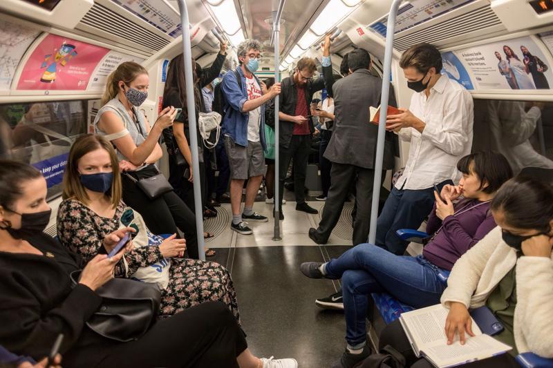 Hành khách đi tàu điện ngầm ở London, Anh hôm 25/8 - Ảnh: Bloomberg.