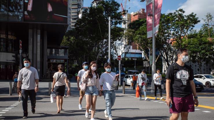 Người dân Singapore đeo khẩu trang để phòng tránh Covid-19 dù tỷ lệ tiêm phòng đạt mức cao - Ảnh: Reuters/CNBC.