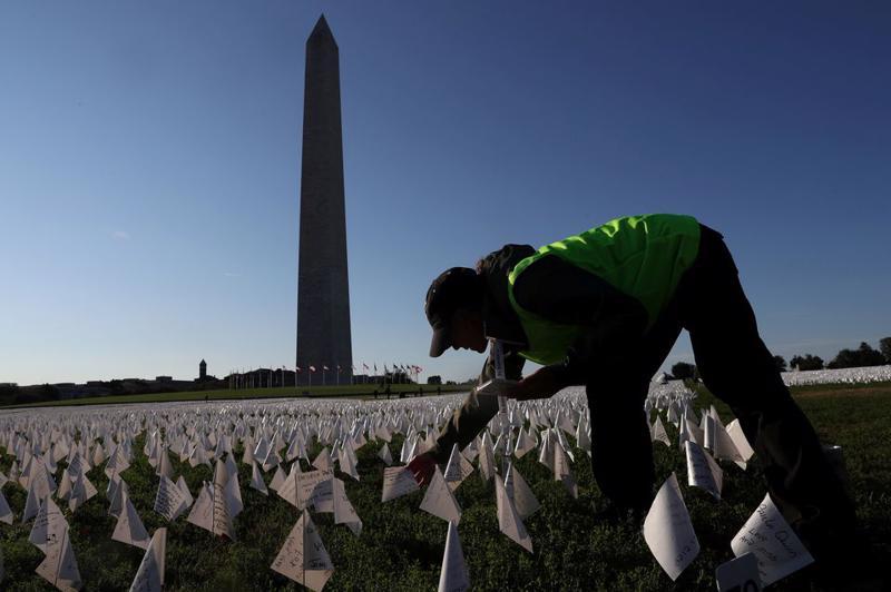 Một tình nguyên viên cắm cờ trắng tại đài tưởng niệm những người đã tử vong vì Covid-19, nằm bên cạnh Đài tưởng niệm Washington ở Washington, Mỹ ngày 1/10 - Ảnh: Reuters