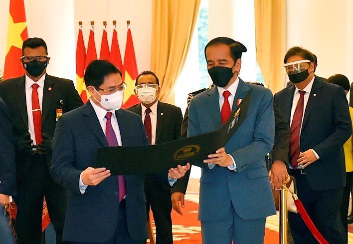 Tổng thống Indonesia Joko Widodo tặng Thủ tướng Phạm Minh Chính tấm hình kỷ niệm cuộc gặp đầu tiên trên cương vị Thủ tướng- Ảnh: VGP