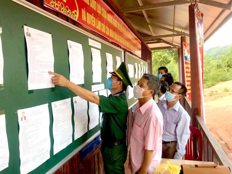 Bộ đội biên phòng và bà con ở xã Thượng Trạch, huyện Bố Trạch, Quảng Bình tìm hiểu các ứng cử viên trước khi ghi phiếu bầu - Ảnh: CTV.