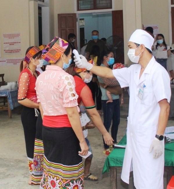 Cán bộ y tế kiểm tra thân nhiệt của cử tri tại điểm bỏ phiếu ở xã Thạch Ngàn, huyện Con Cuông, Nghệ An - Ảnh: CTV.
